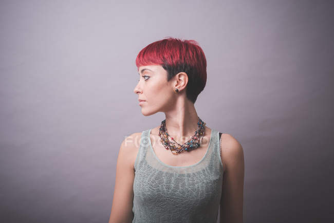 Studio portrait of young woman with short pink hair looking over her shoulder — Stock Photo