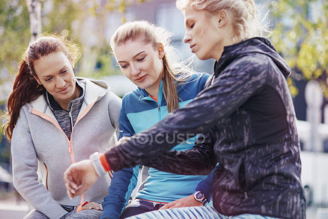 Três corredores femininos coordenação vezes na smartwatch na cidade — Fotografia de Stock
