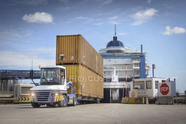 Truck unloading shipping containers from ship to port — Stock Photo