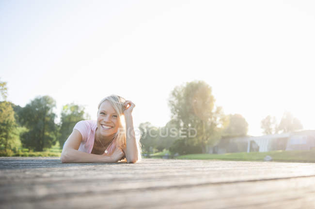 Young woman lying on front smiling, portrait — Stock Photo