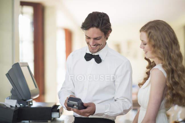 Cameriere e cliente femminile utilizzando la macchina della carta di credito nel ristorante — Foto stock