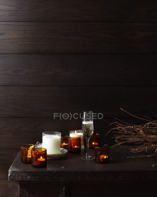 Wooden table with lit candles and glass of champagne — Stock Photo