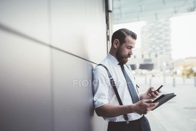 Elegante hombre de negocios con teléfono inteligente y tableta digital fuera de la oficina - foto de stock