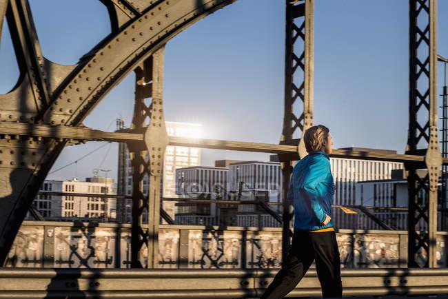 Mann joggt auf Brücke, München, Bayern, Deutschland — Stockfoto