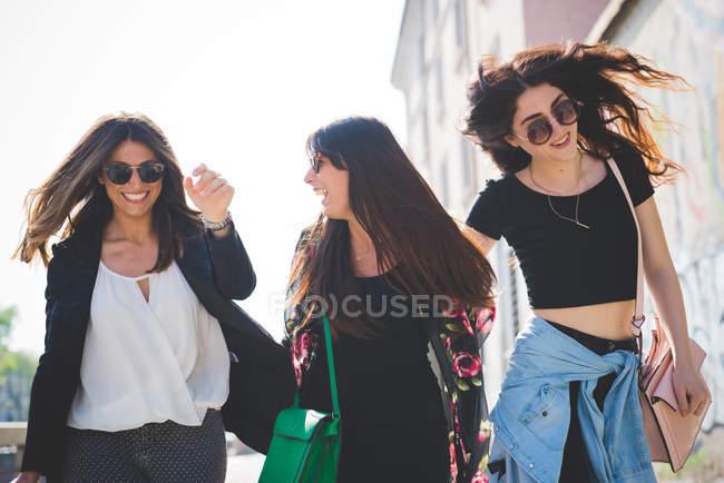 Tre giovani amiche che ridono per strada — Foto stock