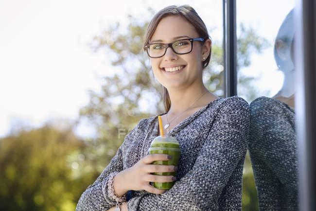 Portrait de jeune femme avec café à emporter appuyé contre le bâtiment du parc — Photo de stock