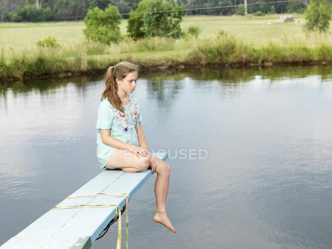 Teenager-Mädchen sitzt auf Sprungbrett über See — Stockfoto