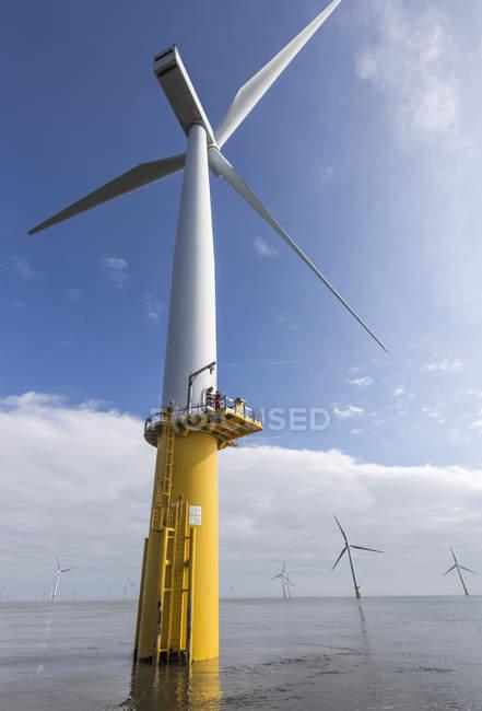 Ingénieur escalade éolienne à partir du bateau au parc éolien offshore — Photo de stock