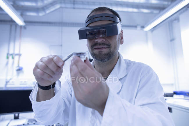 Lab assistant fixing part of professional equipment — Stock Photo