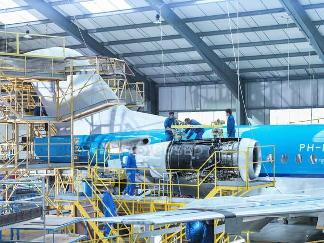 Инженеры сняли реактивный двигатель с самолета на авиаремонтном заводе — стоковое фото