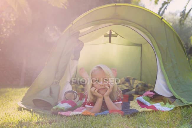Retrato de menina deitada olhando da tenda do jardim — Fotografia de Stock