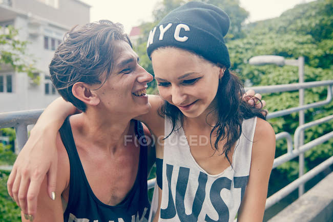 Young couple, smiling with arms around each other — Stock Photo