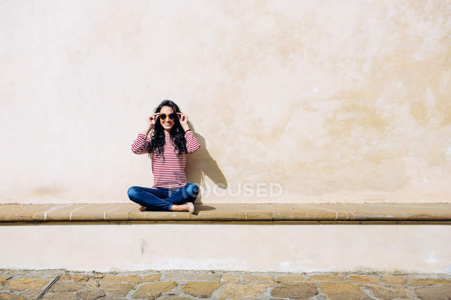 Portrait of young woman adjusting sunglasses on bench, Florence, Italy — Stock Photo