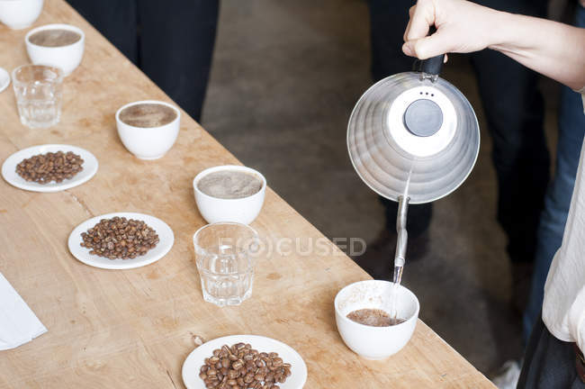 Cropped image of coffee seller pouring hot water into cup of coffee — Stock Photo