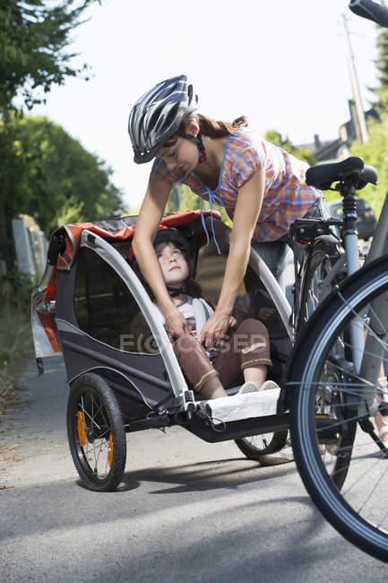 Мать крепления дочери ремень безопасности в велосипеде прицеп — стоковое фото