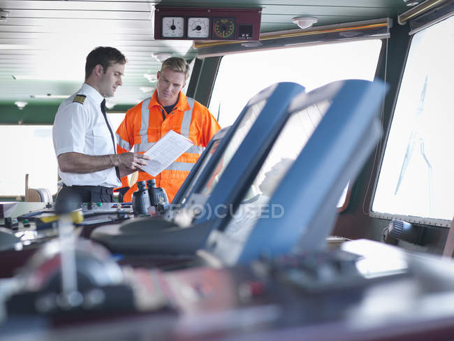 Captain and vessel worker discussing notes on ship bridge — Stock Photo