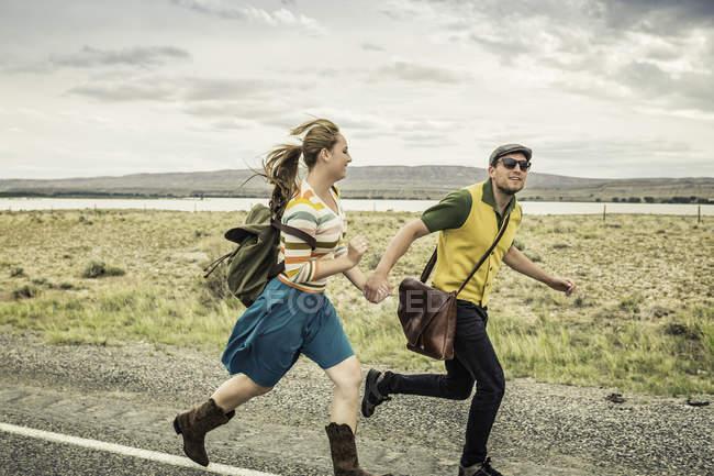 Retro style couple running hand in hand on roadside, Cody, Wyoming, USA — Stock Photo