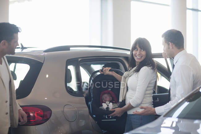 Mid adult couple with baby girl trying out baby seat in car dealership — Stock Photo