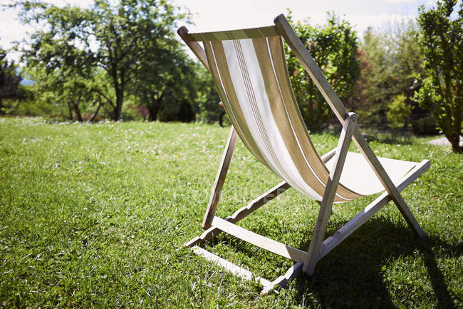 Empty deckchair on sun lighted grass — Stock Photo