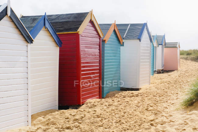 Row Of Multi Colored Beach Huts On Sand Stock Photo