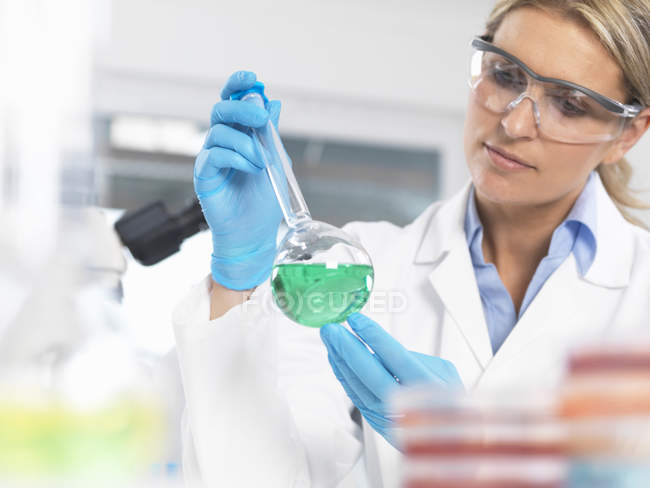 Scientist viewing chemical experiment in a laboratory — Stock Photo