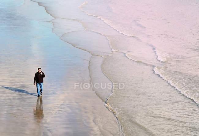 Высокий угол фронта вид зрелого человека, идущего по пляжу вдоль береговой линии — стоковое фото