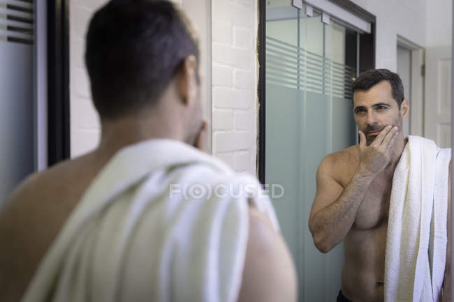 Bare chested mature man looking in mirror, hand on chin, touching stubble, towel over shoulder — Stock Photo