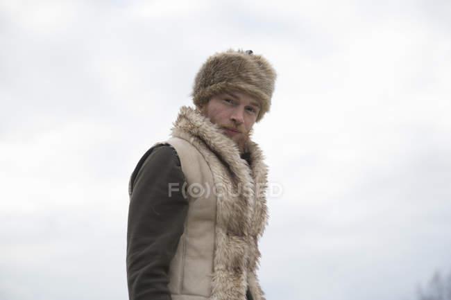 Mitte erwachsener Mann mit pelziger Weste und Trappermütze — Stockfoto