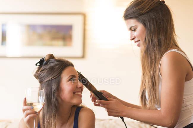 Jeune femme faisant des cheveux ami — Photo de stock