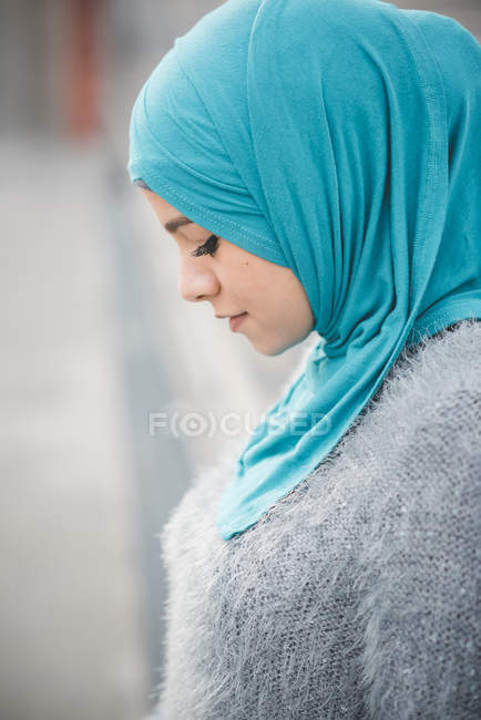 Close up portrait of young woman wearing turquoise hijab on footbridge — Stock Photo
