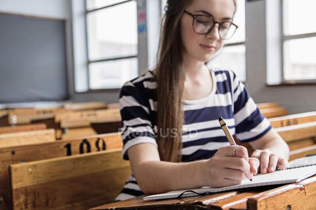 Estudiante trabajando en aula vacía - foto de stock