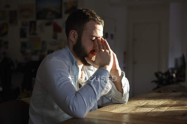 Jovem sentado à mesa da cozinha com as mãos no rosto — Fotografia de Stock