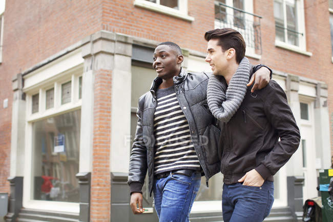Two young men strolling down the street with arms around each other — Stock Photo