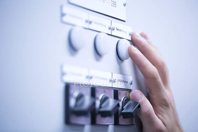 Cropped view of young mans hand adjusting dial on switchgear — Stock Photo
