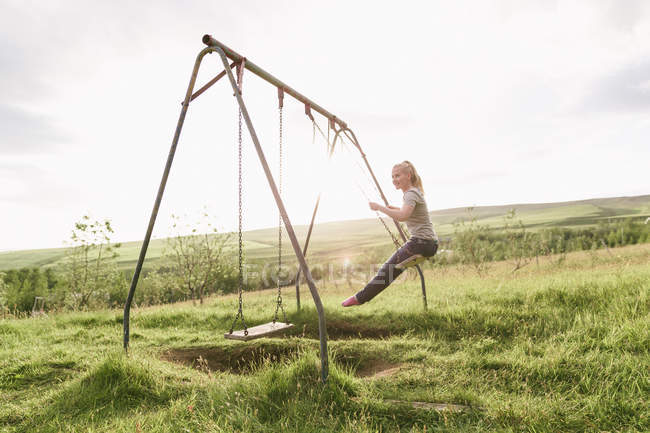 Mid adult woman, in field,  swinging on swing — Stock Photo