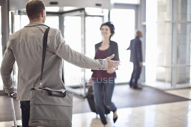 Young businessman opening arms for woman in conference centre atrium — Stock Photo