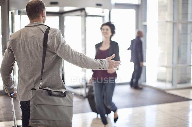 Молодой бизнесмен открывает оружие для женщины в атриуме конференц-центра — стоковое фото