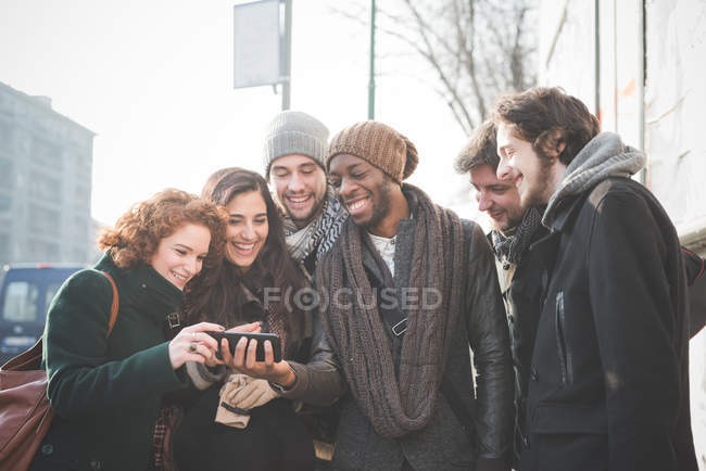 Six young adult friends reading smartphone texts — Stock Photo