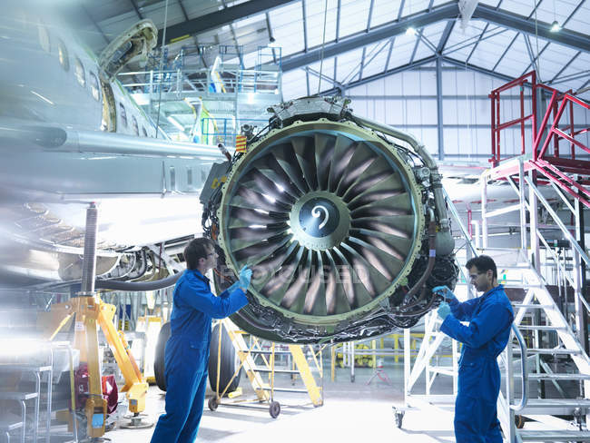 Aircraft engineers working on jet engine in aircraft maintenance factory — Stock Photo