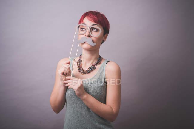 Studio-Porträt der jungen Frau mit Brille und Schnurrbart vor Gesicht — Stockfoto