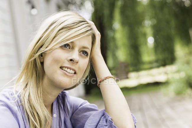 Close up portrait of mid adult woman sitting in garden — Stock Photo