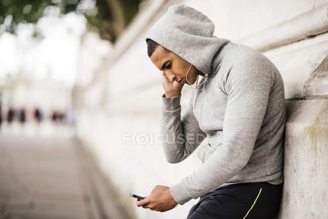 Чоловічий бігун носіння сірий Толстовка читання текстів смартфон — стокове фото
