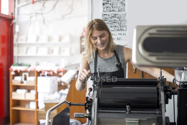 Jovem mulher que trabalha na máquina de impressão tipográfica tradicional na oficina — Fotografia de Stock