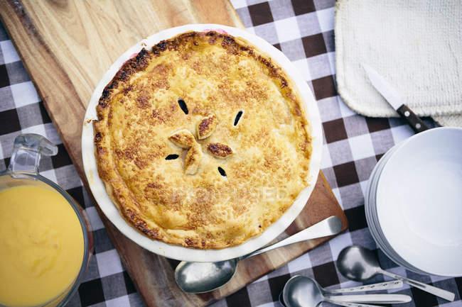 Draufsicht der hausgemachte Kuchen mit Pudding und Löffeln auf Tisch — Stockfoto
