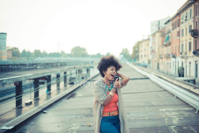 Молодая женщина поет под музыку со смартфона в городе — стоковое фото