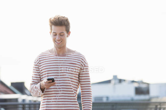 Young man on rooftop, wearing earphones and holding smartphone — Stock Photo