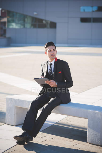 Young businessman using digital tablet on bench — Stock Photo