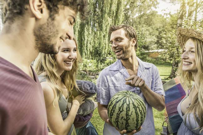Мужчины и женщины в саду держат арбуз — стоковое фото
