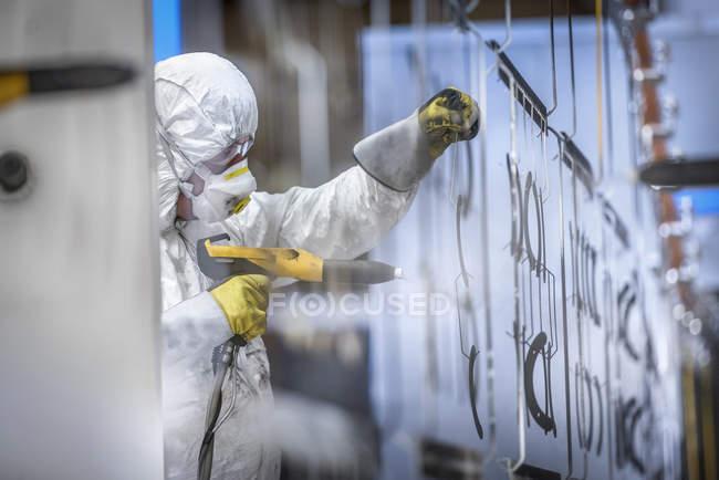 Piezas de recubrimiento en polvo de trabajador en cabina de pulverización de pintura en fábrica de chapa metálica - foto de stock