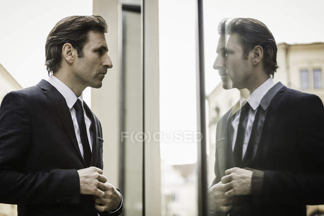 Mature businessman, looking at reflection in window — Stock Photo